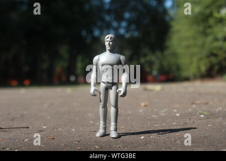 Close up small grey action figure brought to life standing on a park pathway on a bright day - Stock Photo