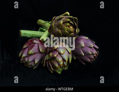Close-up Of Artichokes Against Black Background - Stock Photo