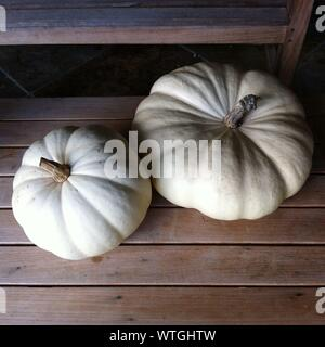 High Angle View Of White Pumpkins On Wooden Table - Stock Photo