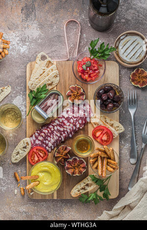 Wine snack set. Glass of wine, meat selection, olives, tomatoes, baguette slices, camembert cheese and spices wooden board. - Stock Photo