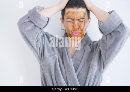 Beautiful young woman wearing cosmetic facial mask as skincare beauty treatment suffering from headache desperate and stressed because pain and migrai - Stock Photo