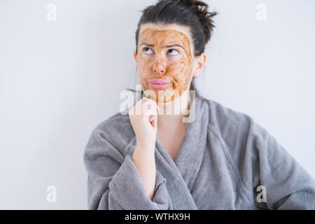 Beautiful young woman wearing cosmetic facial mask as skincare beauty treatment thinking looking tired and bored with depression problems with crossed - Stock Photo
