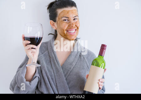 Beautiful woman wearing cosmetic facial mask as skincare treatment drinking glass of wine with a happy face standing and smiling with a confident smil - Stock Photo