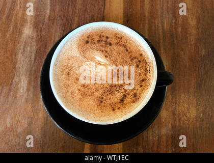Flat lay top view of one Chai Latte in a black cup on saucer served on dark wood stressed cafe table. Popular tea beverage. - Stock Photo