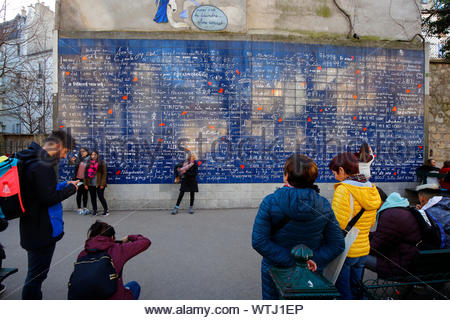 Tourists posing in front of the Wall of Love (le mur des je t'aime) in Jehan Rictus Square in the Montmartre neighborhood of Paris, France - Stock Photo