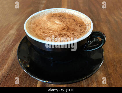 Chai Latte in a black cup on saucer served on dark wood stressed cafe table. Popular tea beverage. Side view. - Stock Photo