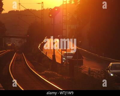Cars Moving On Road By Railroad Tracks During Sunset - Stock Photo