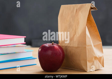 School meal in paper bag on desk - Stock Photo