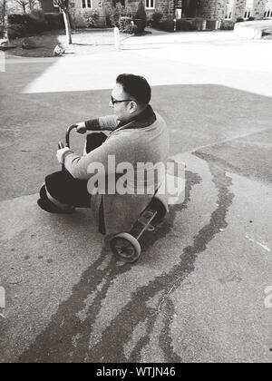High Angle View Of Man Riding Tricycle On Street - Stock Photo