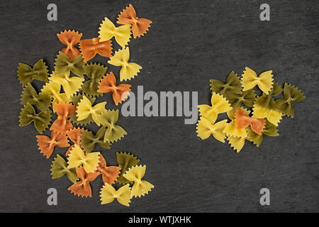 Lot of whole red, yellow and green uncooked farfalle flatlay on grey stone - Stock Photo