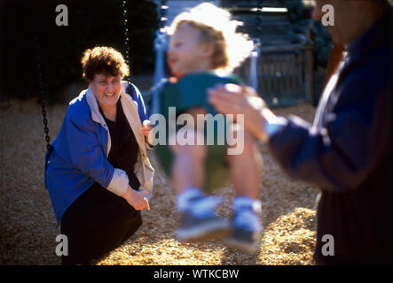 An elderly woman is seated on a swing in a playground. - Stock Photo