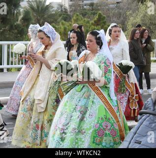 A group of women in traditional dress during Las Fallas, including one looking at a cell phone. - Stock Photo