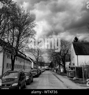 Cars Parked At Roadside Against Cloudy Sky - Stock Photo