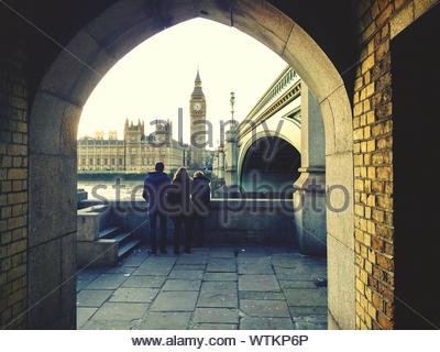 Rear View Of People By Westminster Bridge Looking At Big Ben Seen Through Archway - Stock Photo