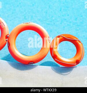High Angle View Of Life Belts Floating On Swimming Pool - Stock Photo