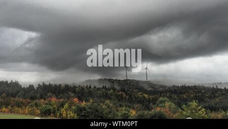 Distant View Of Wind Turbines On Landscape Against Cloudy Sky - Stock Photo