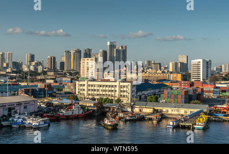 Manila, Philippines - March 5, 2019: South Harbor evening twilight. Lots of activity of boats, trucks, cranes, containers and more. Horizon is line of - Stock Photo