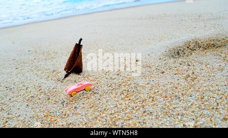 High Angle View Of Pink Toy Car On Beach By Sea - Stock Photo