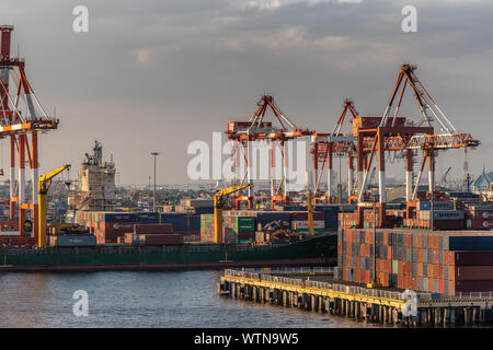 Manila, Philippines - March 5, 2019: South Harbor evening twilight. Combination of shipping containers, multiple cranes, and ships under cloudscape. - Stock Photo