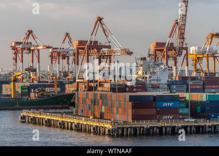 Manila, Philippines - March 5, 2019: South Harbor evening twilight. Closeup of combination of shipping containers, multiple cranes, and ships under cl - Stock Photo