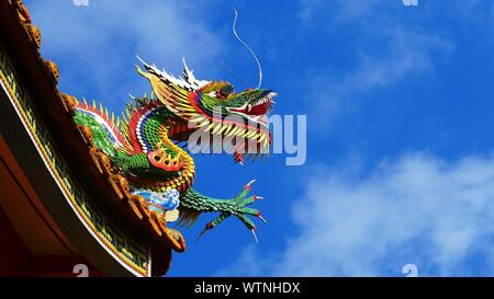 Low Angle View Of Chinese Dragon On Roof Against Blue Sky Stock Photo