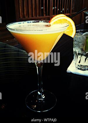 Close-up Of Cocktail With Lemon Slice Served On Table In Nightclub - Stock Photo
