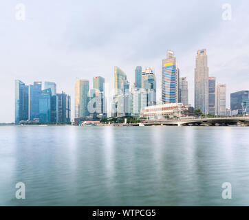 Singapore - 5 Sep 2019: Singapore iconic skyline is reflected in the Marina Bay waters at sunrise, with the Sands Resort, the ArtScience Museum - Stock Photo
