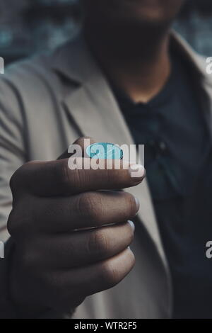 Midsection Of Businessman Holding Coin - Stock Photo