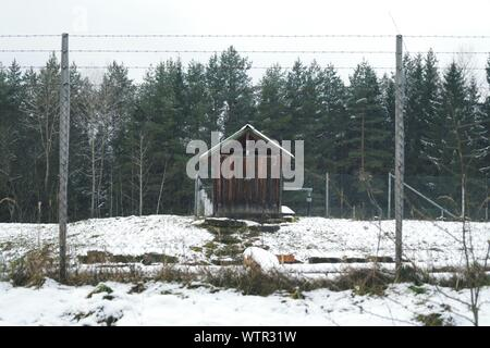 Chainlink Fence In Front Of Barn During Winter - Stock Photo