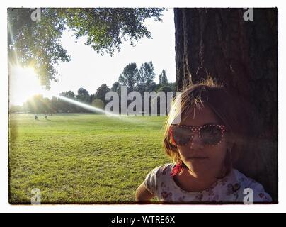 Close-up Of Girl Wearing Sunglasses Standing By Tree In Park - Stock Photo