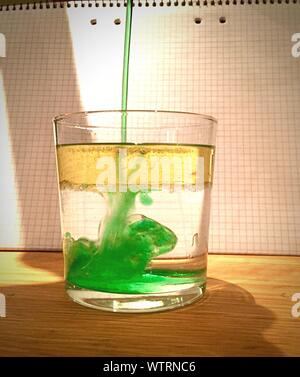 Green Liquid Poured In Glass Water - Stock Photo