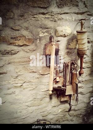 Kitchen Utensils Hanging On Stone Wall - Stock Photo