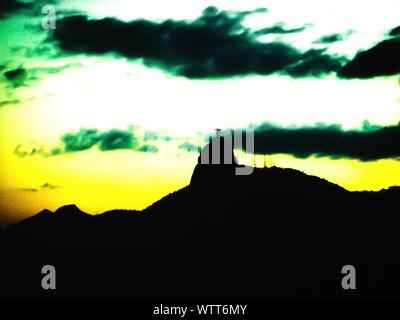 Low Angle View Of Silhouette Christ The Redeemer Statue On Top Of Mountain Against Cloudy Sky - Stock Photo