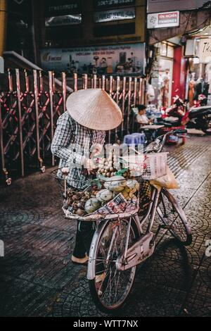 Vendor In Asian Style Conical Hat Selling Food On Bicycle At Street - Stock Photo