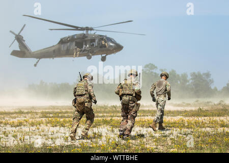 Advisors from 1st Security Force Assistance Brigade, approach a A UH-60L Black Hawk for sling load transportation during the Advisor Forge training exercise at Fort Benning, GA,  August 13, 2019. The group of advisors were tasked with connecting the load to the helicopter undercarriage. (U.S. Army photo by Pfc. Daniel J. Alkana/ 22 Mobile Public Affairs) - Stock Photo