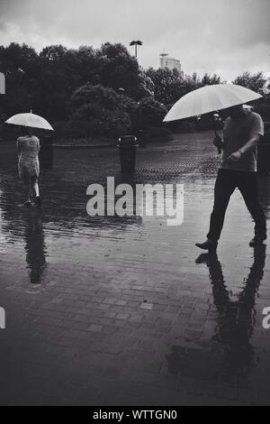 People Walking On Wet Street With Umbrella During Monsoon At Dusk - Stock Photo