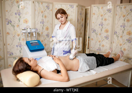 Vacuum massage device . Anti cellulite body correction treatment. Loss weight apparatus. Woman and doctor at medicine salon. Beauty saloon. vacuum massage of the abdomen. Anticellulite massage. - Stock Photo