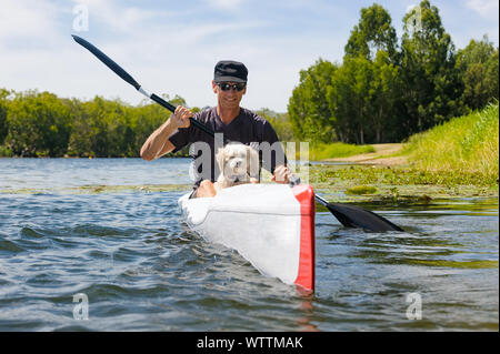 Man and his best friend paddling down the Ross River in Townsville on a ski. - Stock Photo