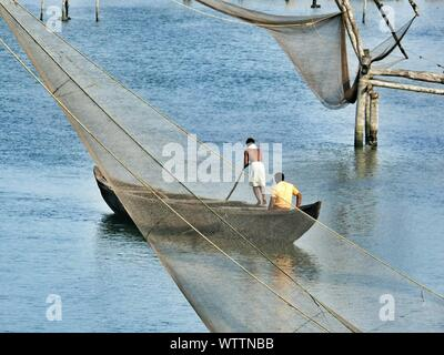 Fishing Net Against Men On Boat Sailing In River - Stock Photo