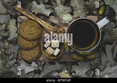 Top compositions view of boiled acorn coffee in metal mug, brown sugar cubes, wooden spoon, biscuits on wooden plate and all elements surrounded with - Stock Photo