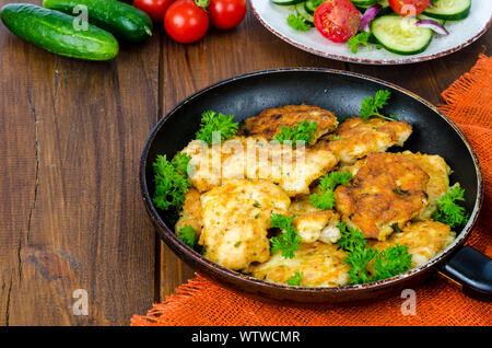 Fried meat pancakes in pan, vegetables, wooden background - Stock Photo