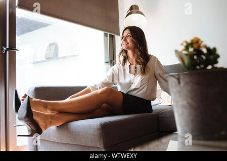Brunette woman with office clothes taking off her shoes on a couch.
