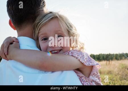 portrait of a young girl being carried by her father at sunset - Stock Photo