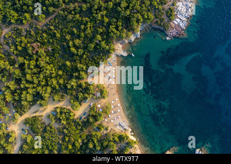 Aerial drone view of beach umbrellas and sunbeds on the coast in Thassos island, Greece - Stock Photo
