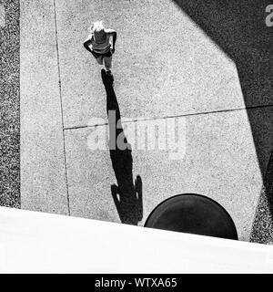 Directly Above Shot Of Woman Jogging On Street - Stock Photo