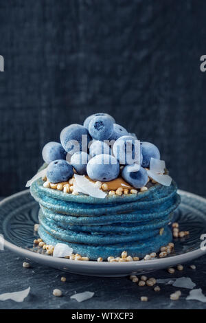 Blue spirulina pancakes topped with peanut butter, blueberries and coconut chips - Stock Photo