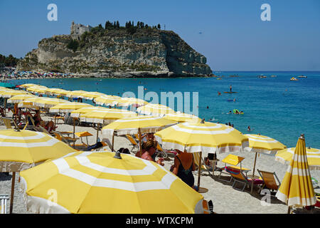 Public beach in Tropea, Calabria, Italy. View from North in August 2019, with the hill with the Church of Santa Maria from Island, at the back - Stock Photo