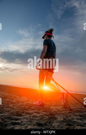 woman doing Nordic walking by the beach in the morning - Stock Photo