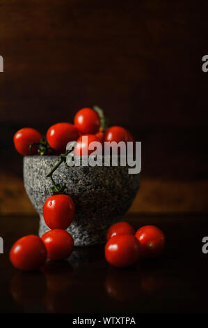 Small, bright red tomatoes on the branch shot in a grey stone bowl with wood background. Fruits are reflected in the table. Natural light. - Stock Photo