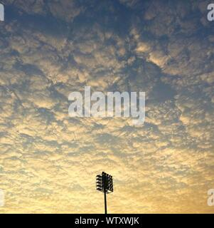 View Of Floodlights Against Cloudy Sky - Stock Photo